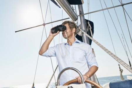 Mann mit Fernglas am Ruder eines Segelboots