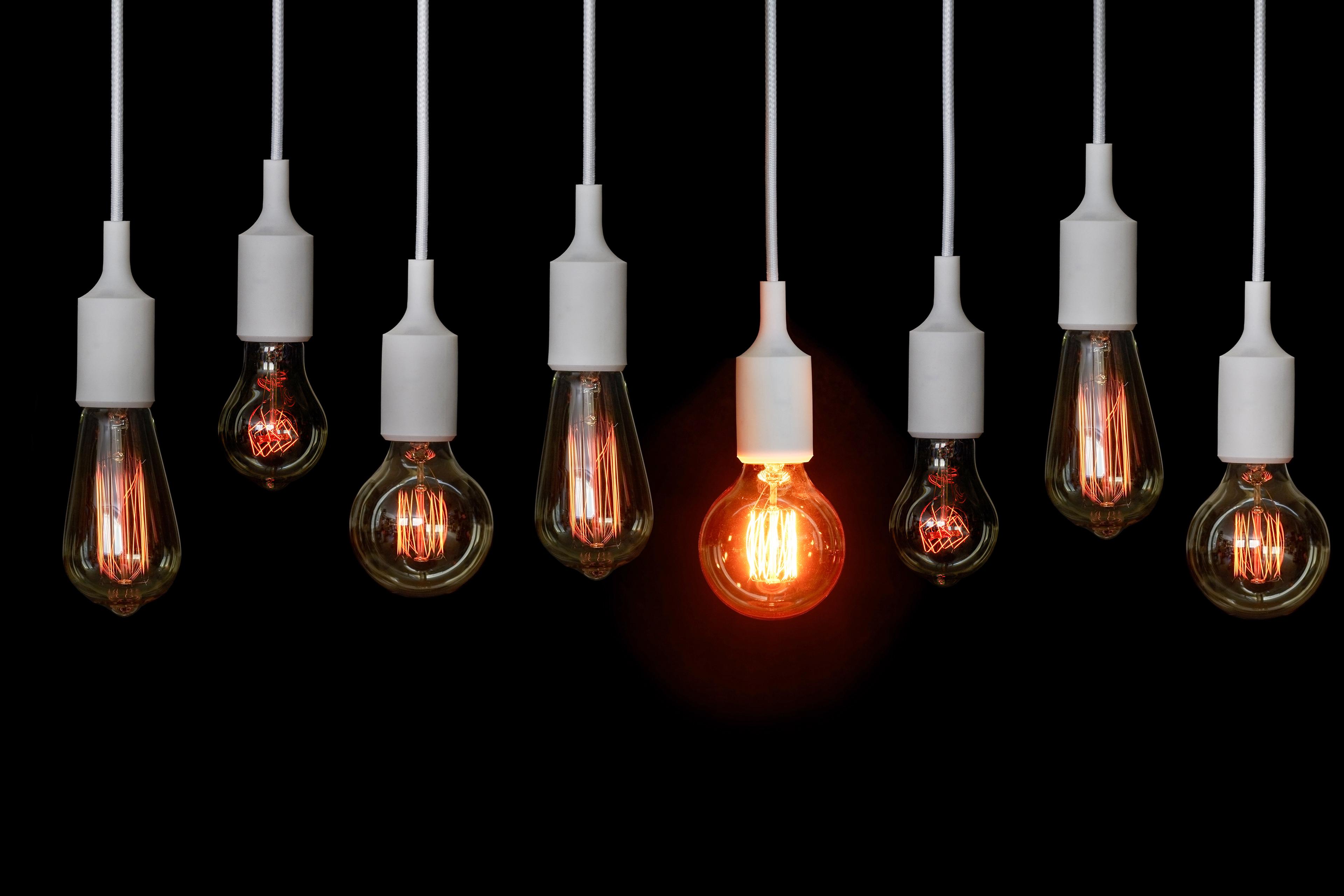 Reihe von Glühbirnen und eine leuchtet