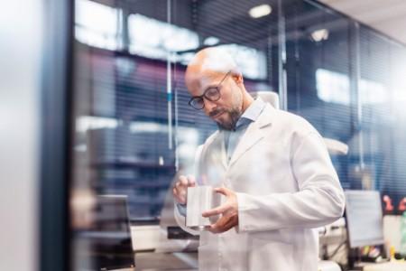 Techniker, der einen Laborkittel trägt und das Werkstück untersucht