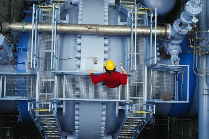Arbeiter kontrolliert Ventil an Wasserkraftwerk