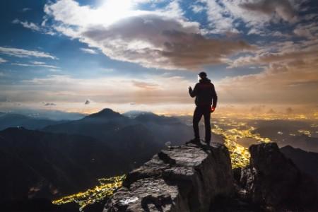 Wanderer schaut auf erleuchtete Stadt