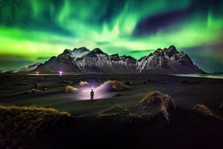 man watching aurora over mountains