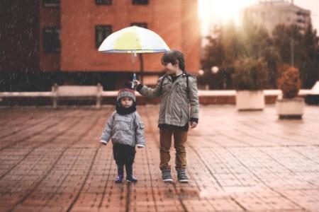 Brüder stehen unter einem Regenschirm