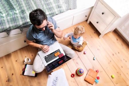 Vater im Homeoffice auf dem Boden sitzend mit seinem Baby neben sich