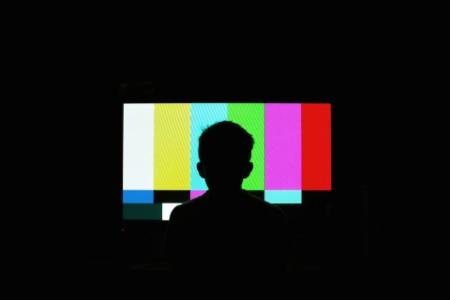 Person sitzt im Dunkeln vor TV, welcher nur Farben anzeigt