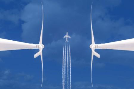 Zwei Windräder und ein Flugzeug in der Luft