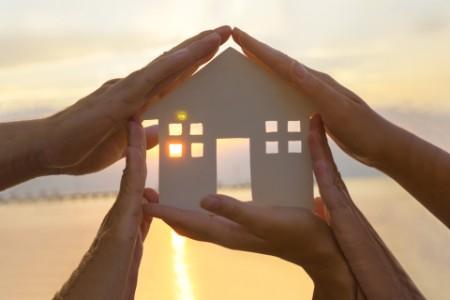 Handflächen auf allen Seiten eines ausgeschnittenen Hausdiagramms mit untergehender Sonne, die durch ein Fenster über Wasser kommt