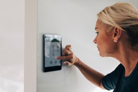 Eine Frau bedient ein Smart-Home-Panel.