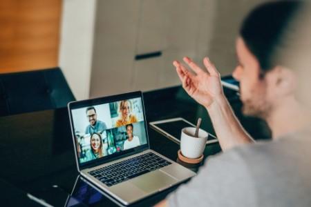 Gruppe von Menschen, die einen Laptop für ein Online-Meeting per Videoanruf verwenden.