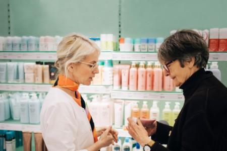 Apothekerin verkauft ein Medikament an eine Kundin