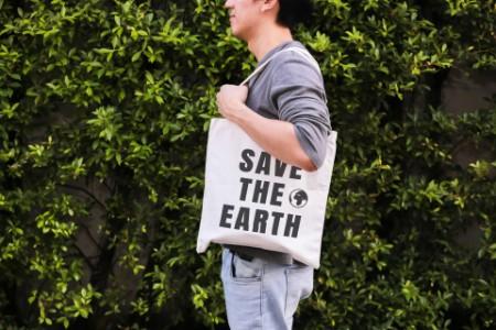 Person stehend vor einem grünen Hintergrund mit Tasche aus Stoff
