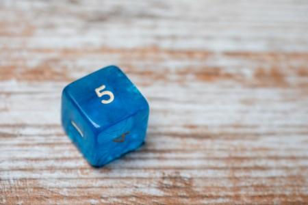 Blauer Würfel auf Holztisch