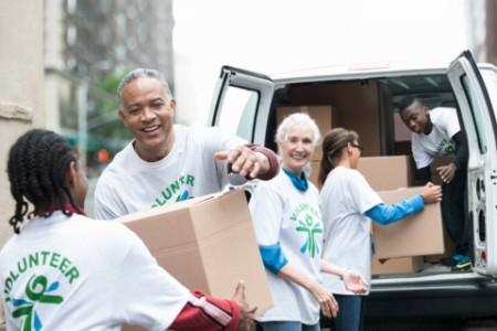 Freiwillige Helfer reichen Kartons vom Lieferwagen
