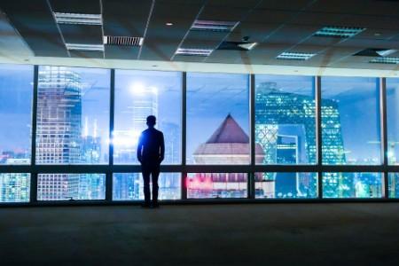 Mann steht vor Fensterfront