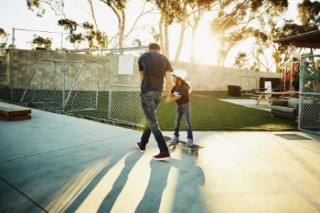 Mann hilft seiner Tochter auf dem Skateboard