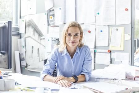 Frau sitzt mit Ordnern am Schreibtisch