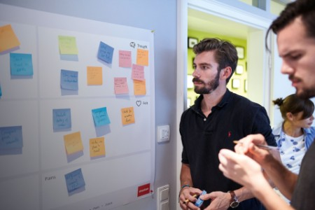 event attendees look at a board with sticky notes