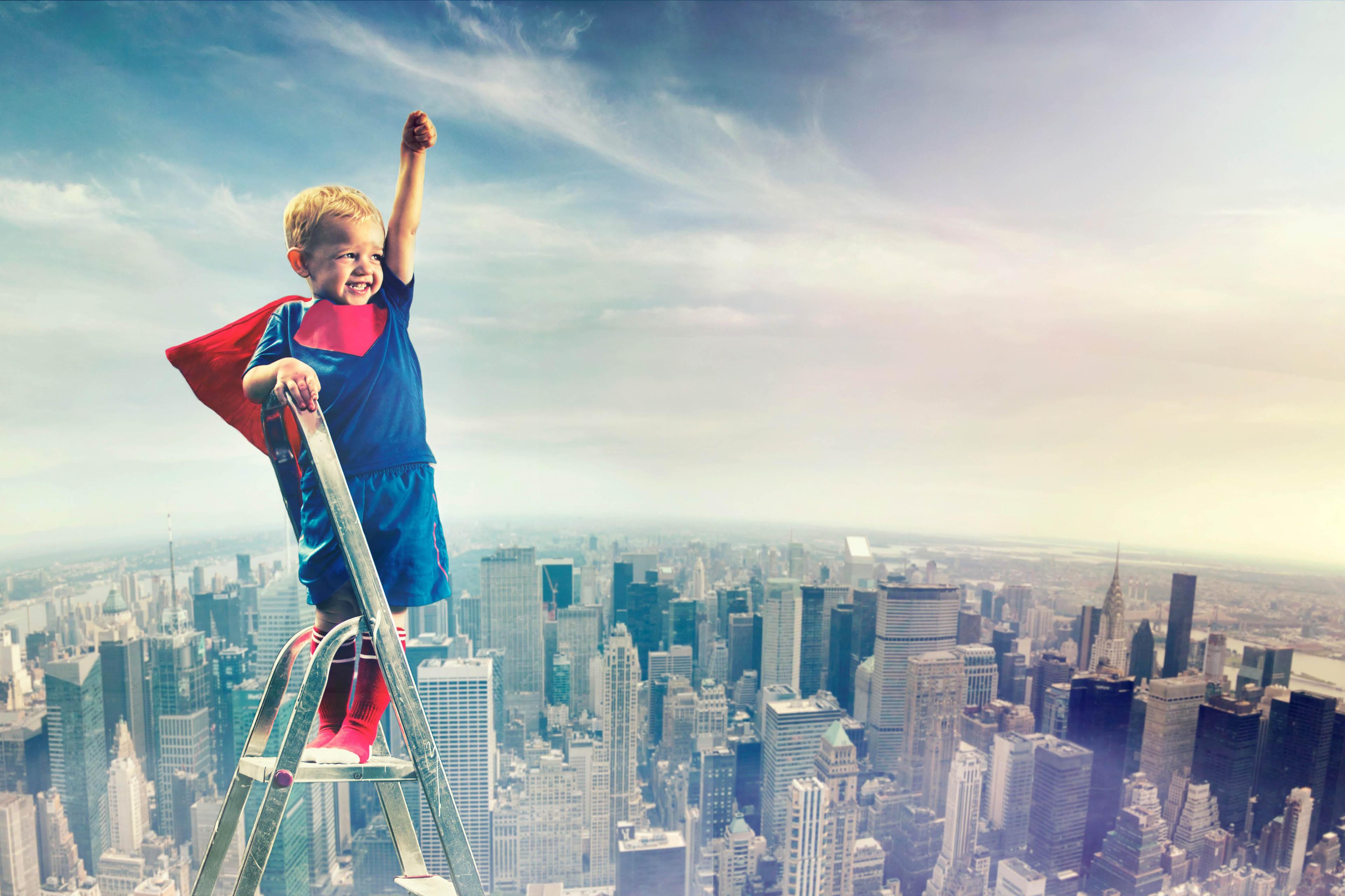 Small boy superhero climbing