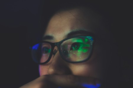 Photographic image of screen reflecting on person's glasses