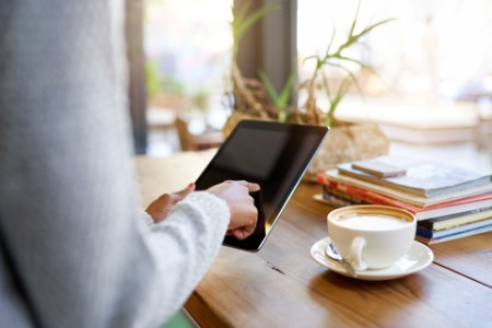 Closeup of a young woman sitting at a table in a cafe using a digital tablet