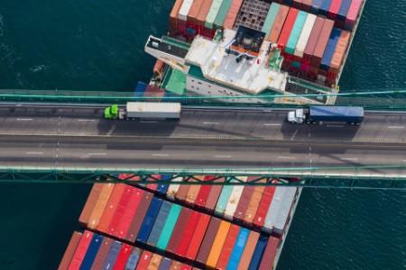 Küresel tedarik zincirini betimleyen köprü üzerinde kamyonlar ve altlarındaki kargo gemisi