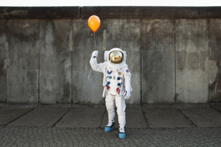 An astronaut on a city sidewalk holding a balloon
