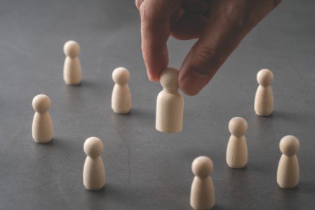 Business & HR global wood puzzle concept for leadership and team with peg doll and hand