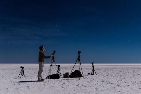 EY - Man in desert photographing the night sky