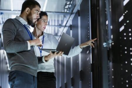 Un homme et une femme devant un mur de serveurs informatiques