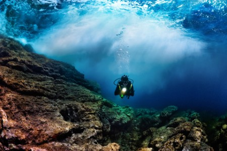 EY - Scuba diver in front of a dramatic wave