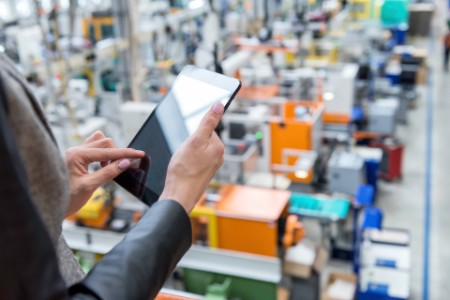 EY - Female manager working on tablet in factory