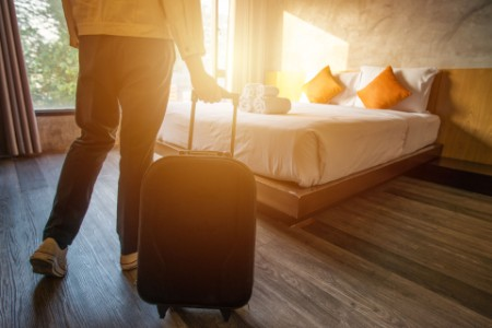 EY - Woman pulling her luggage to her hotel bedroom