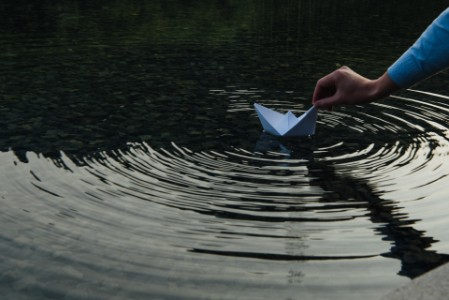 EY - Person Holding Paper Boat In Lake