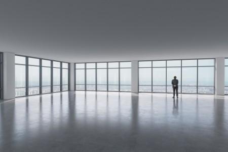EY businessman standing in empty office