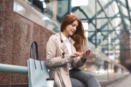 EY - Business woman using smart phone city street