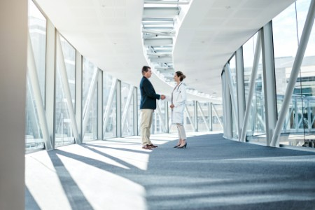 Shot of a well dressed man shaking hands with a female doctor
