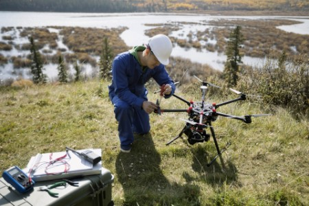 Surveyor repairing drone equipment on hilltop overlooking lake