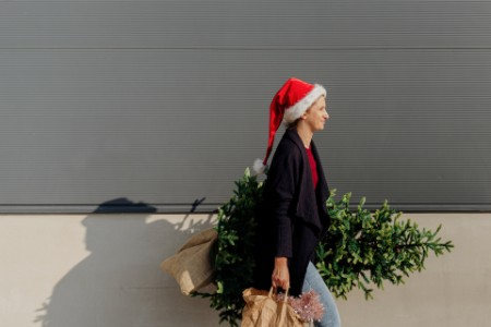 Photo of young woman carrying Christmas tree after shopping