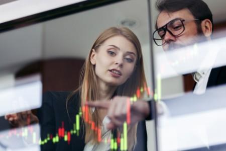 Businesswoman and businessman talking profit on futuristic display