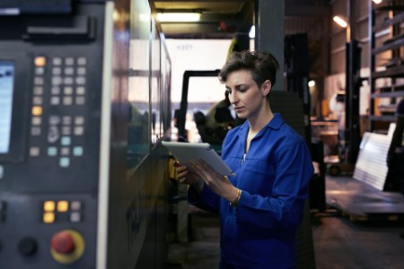 Female steel worker holding tablet inside factory