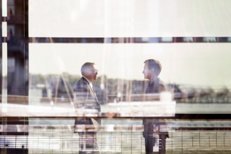Two businessman talking by the window.