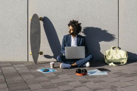 Junger Geschäftsmann sitzt im Freien an einer Wand und arbeitet am Laptop