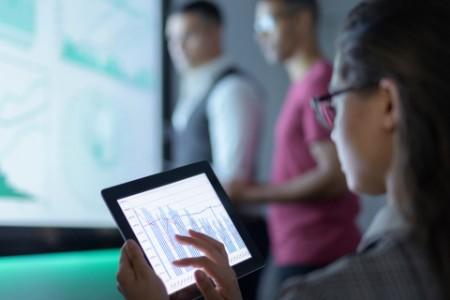 Geschäftsfrau, die bei einem Geschäftstreffen Diagramme auf einem digitalen Tablet betrachtet