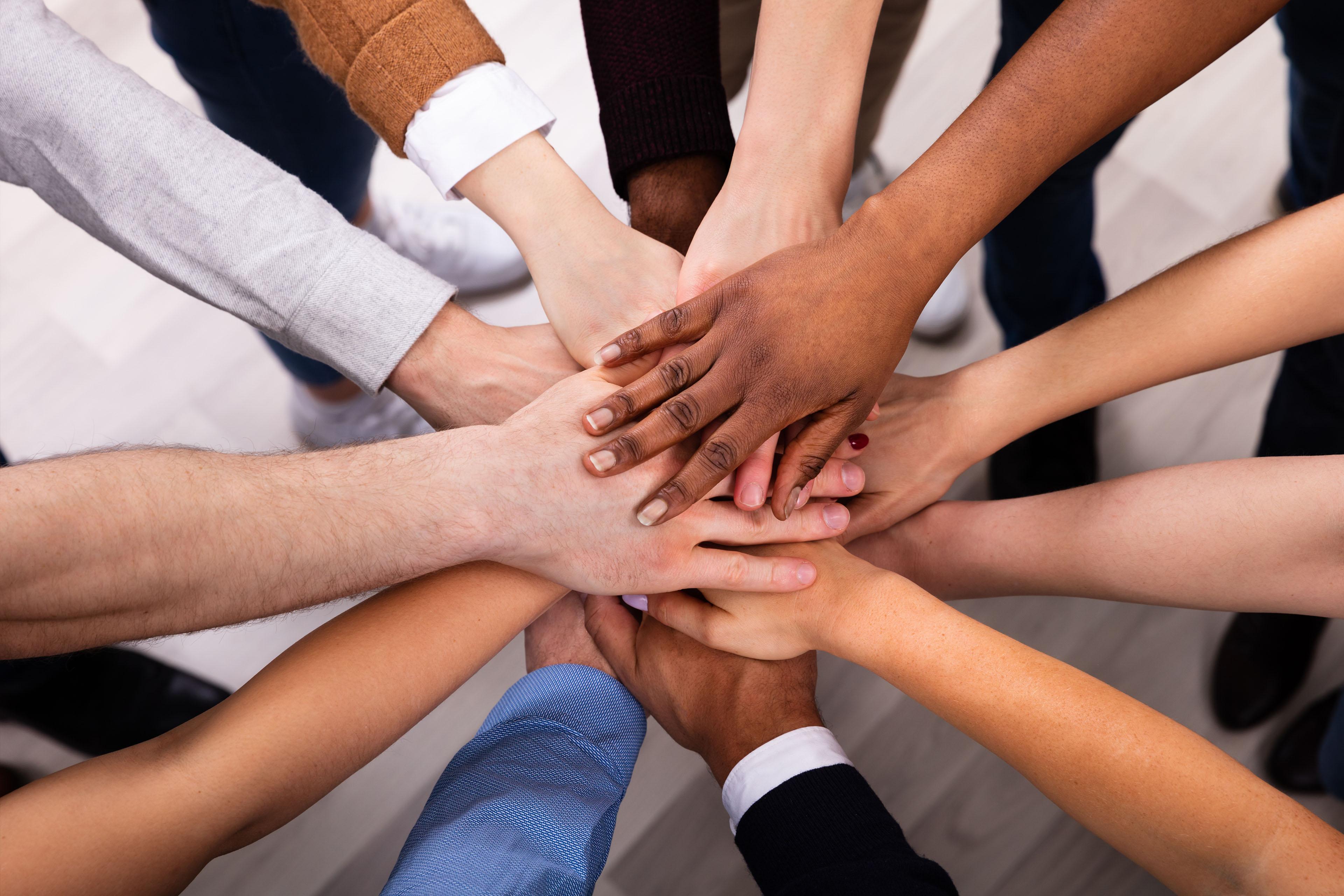 Diversas personas apilan sus manos