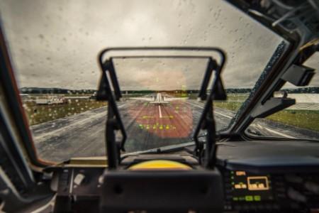 Avión en pista de aterrizaje con vista al cielo a través de un parabrisas húmedo