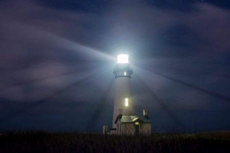 Illuminated yaquina head lighthouse against sky night