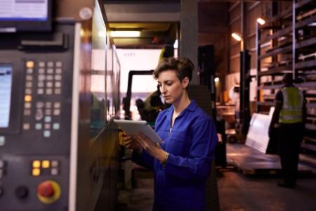 Female steel worker holding tablet inside factory article