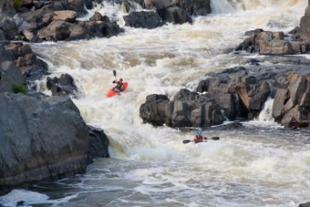 Kayakers going through big river rapid