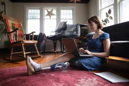 woman using laptop living room floor