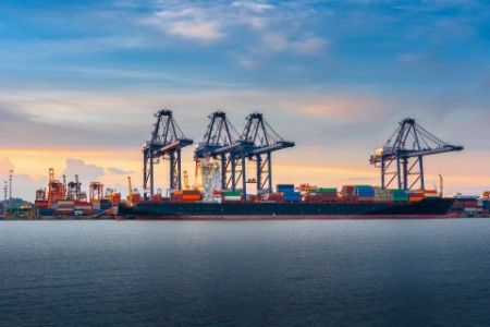 Container ship being loaded at port by cranes